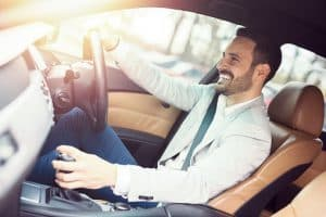 Young handsome businessman is driving a car looking very happy.